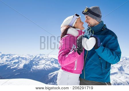 Young couple looking at each other and holding snow heart. Smiling man and woman in winter clothing holding snowy heart at mountain. Loving couple in romantic winter holiday with copy space.