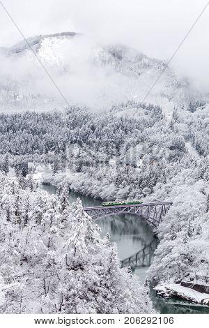 Winter landscape snow covered trees with train crossin River on Bridge