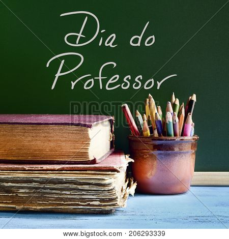 closeup of a chalkboard with the text dia do professor, teachers day written in Portuguese, a pile of old books and a pot with pencils on a rustic wooden table