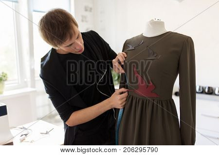 tailoring, sewing and clothing concept - fashion designer with dummy and measuring tape making new dress at home studio or workshop
