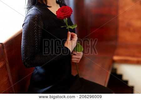 people, grief and mourning concept - close up of woman with red roses sitting on bench at funeral in church