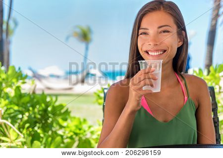 Woman drinking cold water drink glass at outdoor cafe hotel resort on beach holidays. Healthy girl staying hydrated during warm summer heat on tropical vacation, Caribbean weather.
