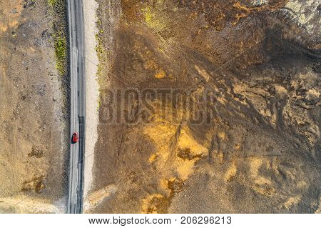 Open road with car driving on travel adventure aerial view of desert landscape for vacation concept. Highway crossing through lava rocks volcanic mountains, nature background in Iceland.