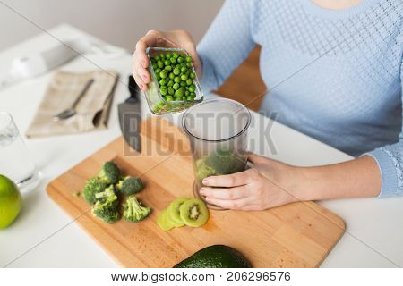 healthy eating, baby food, diet and cooking concept - close up of woman hand adding pea to measuring cup with broccoli