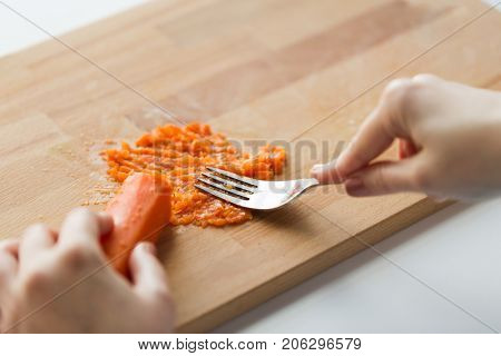 baby food, healthy eating and nutrition concept - hand with fork making mashed carrot on wooden board