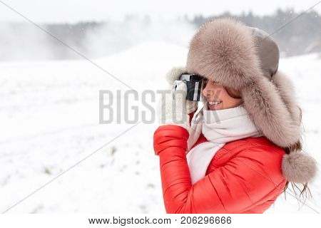 people, photography and leisure concept - happy woman in winter fur hat with film camera photographing outdoors