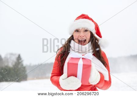 holidays and people concept - happy woman in santa hat with chrismas gift outdoors in winter