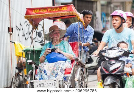 HANOI VIETNAM - AUGUST 2017: Caucasian tourist travelling by cyclo in the Old quarter of Hanoi