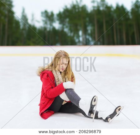 sport, trauma and winter concept - young woman with knee injury suffering from pain on skating rink