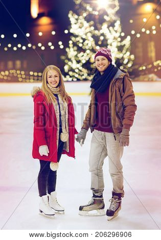 holidays and leisure concept - happy couple holding hands on skating rink over christmas tree background
