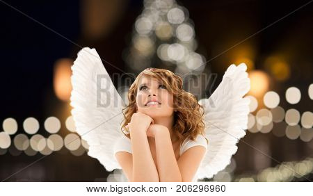 holidays, christmas and people concept - happy young woman or teenage girl with angel wings over lights background