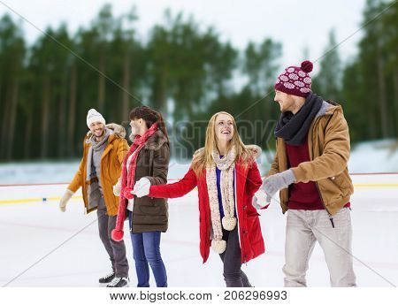 friendship, winter and leisure concept - happy friends holding hands on skating rink over outdoor background