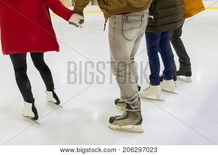 people, winter and leisure concept - close up of friends on skating rink