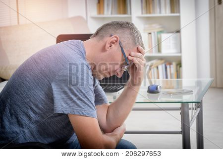 Freelancer man at workplace with headache holding his head on hands. Overworking, mistake, stress and depression concept