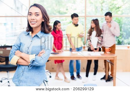 Portrait of young Asian woman looking at camera with self-confidence and determination as member of a young creative team
