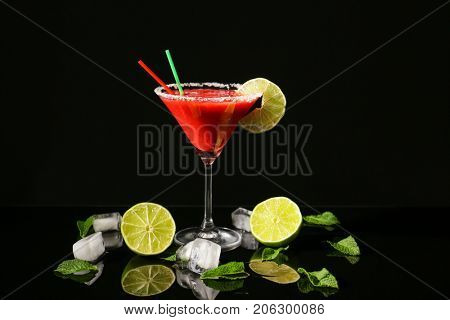 Glass of delicious strawberry daiquiri with lime and ice cubes on black background