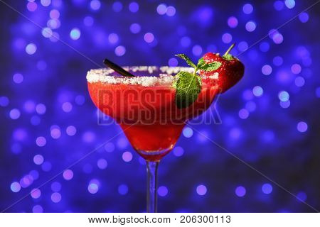 Glass of delicious strawberry daiquiri against defocused lights
