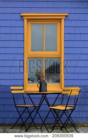 Patio table and window in complementary colours of yellow and purple