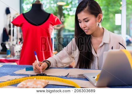 Asian fashion designer preparing drafts for cut-outsor her new collection