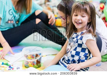 Cheerful pre-school girl wearing a trendy T-shirt while playing on the floor, supervised by her young and cool female teacher in a modern kindergarten