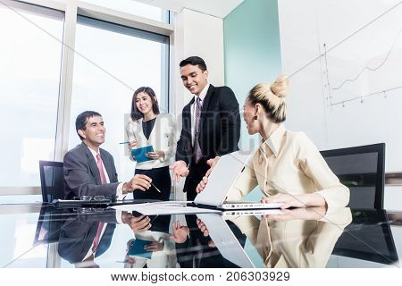 Group of Asian business women and businessmen negotiate contract in conference room office