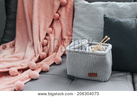 Knitted basket with yarn and needles on grey sofa by the warm pompon blanket and cushions. Still life photo of nordic interior details. Cosy place in winter decorated room.