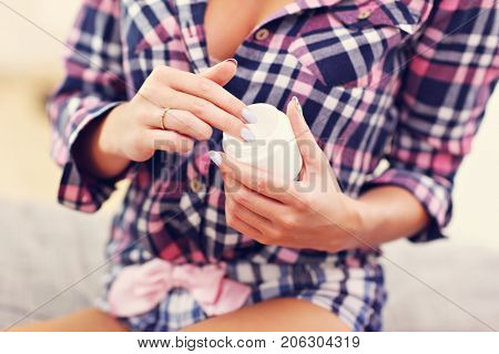 Midsection of sexy woman in pyjamas holding body balm