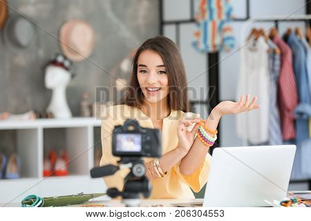 Young female blogger with accessories recording video at home