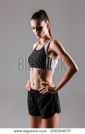 Portrait of a young attractive fitness woman posing while standing with hands on hips isolated over gray background