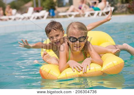 Two Happy Children Playing On The Swimming Pool At The Day Time.