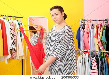 Beautiful overweight woman near rack with small-sized clothes at store