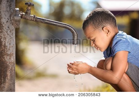 African American child drinking water from tap outdoors. Water scarcity concept