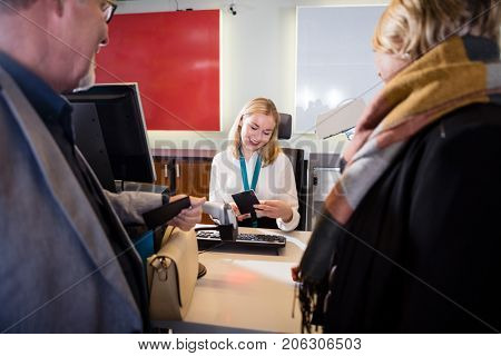 Staff Checking Passport Of Passengers At Airport Check-in