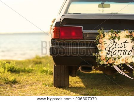 Beautiful wedding car with plate JUST MARRIED on shore
