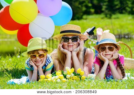 Happy summer day. Cheerful girls resting with their beloved mother in the park. Family concept.