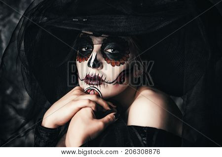 Portrait of a beautiful and scary Calavera Catrina in black dress and black hat with a veil over dark background. Sugar skull makeup. Dia de los muertos. Day of The Dead. Halloween.