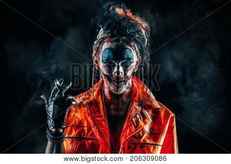 Halloween. Portrait of a disgusting clown man smoking a cigar over black background. Male zombie clown. Horror, thriller film.