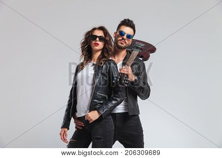 arrogant rock and roll couple looking down to you on grey background