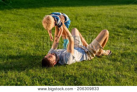 Happy man and child having fun outdoor on meadow.  Family lifestyle scene of father and son resting together on green grass in the park.