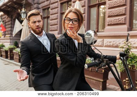 Displeased bearded business man sitting on modern motorbike outdoors with elegant woman which looking at mirror