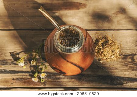 Argentinean yerba mate drink with chamomile flowers, high angle view