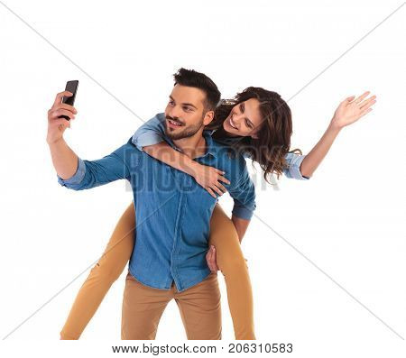 woman on the back of man waving at the camera while he takes a selfie with his phone on white background