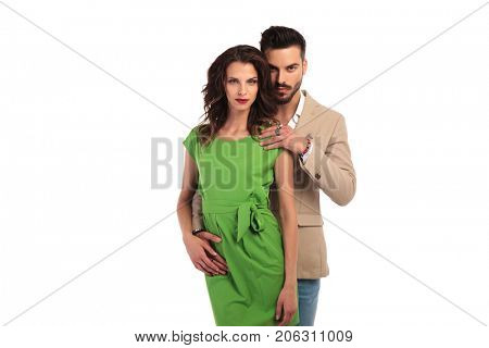 young sexy couple looking at the camera, man behind woman wit hand on her shoulder, on white background