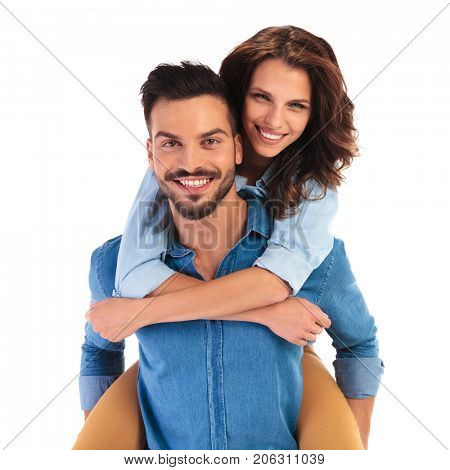 happy smiling young casual couple on white background, woman on the back of her boyfriend