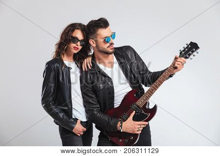 man playing his electric guitar for his woman on grey studio background; rock and roll couple
