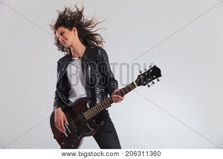 happy head banging woman guitarist playing on her electric guitar on grey background