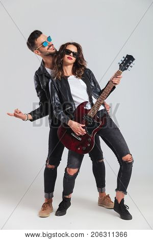 man making rock and roll gesture while woman is playing her electric guitar in studio