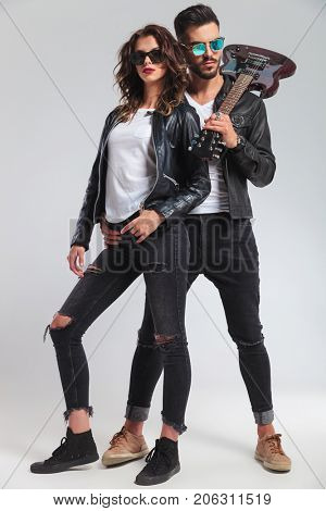 rock and roll man with guitar on shoulder embracing his woman; cool punk couple on grey background