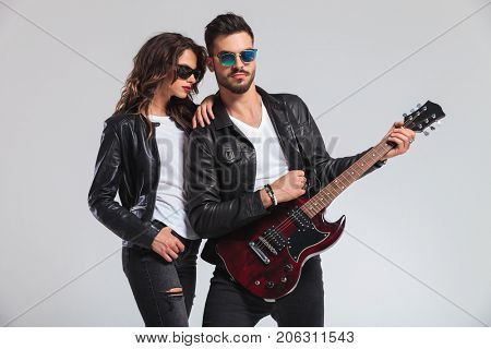 woman leaning on man's shoulder while he is playing an electric guitar; rock and roll couple