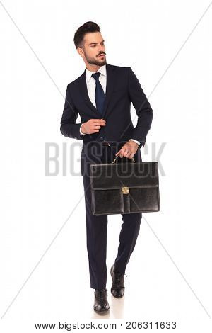 young fashion business man walking with briefcase and looks to side on white background